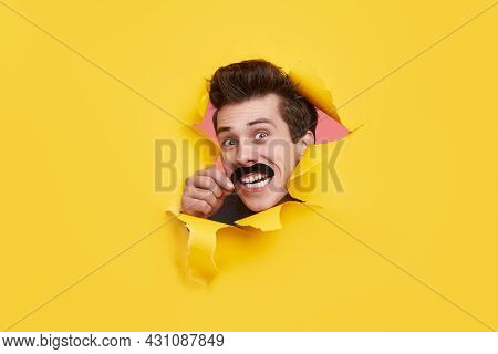 Excited Young Guy With Fake Mustache Looking At Camera With Astonished Face Expression Through Rippe