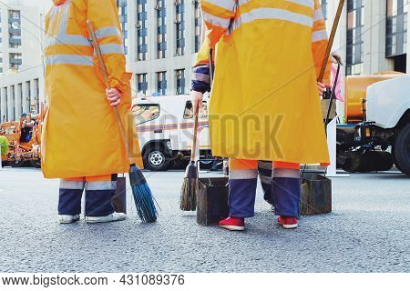 The Back View Close Up Of Municipal Workers In Orange Uniform Sweep City Streets With Manual Cleanin