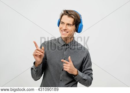 Happy Smiling Young Guy In Grey Shirt Standing Listening Music Wearing Blue Wireless Headphones Poin