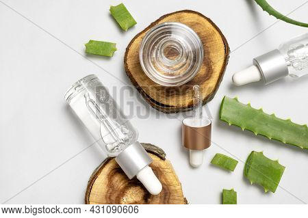 Natural Cosmetics Concept. Cosmetic Oil, Serum, Gel With Aloe Vera Extract In Glass Container With P