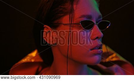 Night Portrait Of Girl And Neon Lights. Portrait Shot Of A Beautiful Girl Wearing Down Jacket And Su