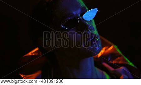 Portrait Shot Of A Beautiful Girl Wearing Down Jacket And Sunglasses In Neon Color Lights . Pretty G