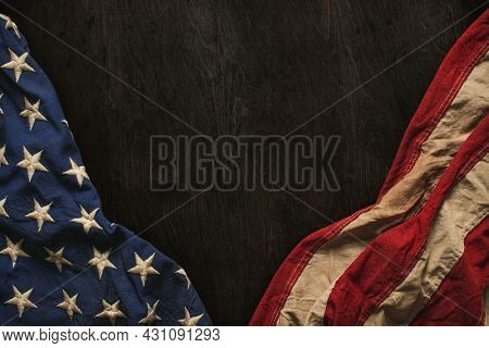 Vintage US American flag crumpled on worn wooden background. Blank copy space for text. For USA Memorial day, Veterans day, 4th of July, or other patriotic holiday.