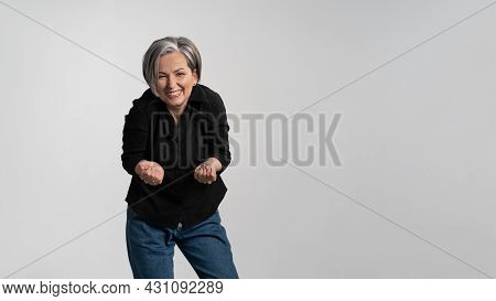 Happy To See Her Grand Kids Bowed And Hands Stretched Forward Grey Haired Mature Woman Wearing Black