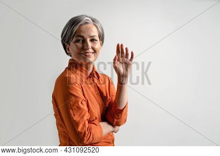 Happy Middle Aged Grey Haired Woman Smile Looking At Camera With One Hand Lifted Up In A Folded Arms