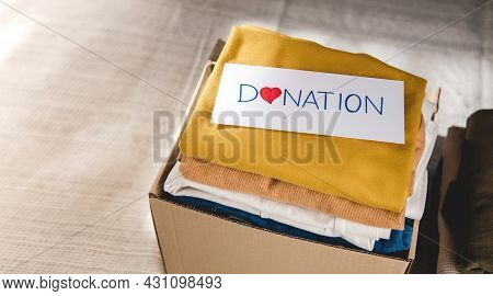Clothes Donation Concept. Box Of Cloth With Donate Label. Preparing Used Old Garment At Home. Top Vi