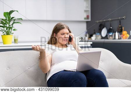 Talking On The Phone While Working On Laptop Sitting At Home Overweight Young Woman Staying At Home