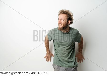 Leaned On The Wall And Looking Sideways Handsome Young Man With Curly Hair In Olive T-shirt Isolated