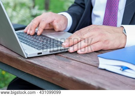 Close-up Of Male Hands On The Laptop Keyboard. A Man In A Business Suit And Tie Works On The Open Ve