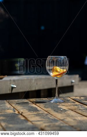 Vertical Photo Of Empty Wine Glass On Wooden Table. Unfilled Cut-glass With Orange Slice At Rustic W