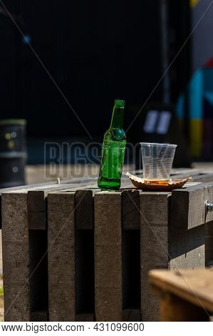 Vertical Photo Of Empty Green Bottle And Plastic Cup On Rustic Table. Unfilled Bottle Of Bear With E
