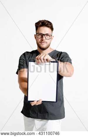 Male Physician Practitioner Showing Blank Space Sheet For Clinic Advertising. Studio Portrait On Whi