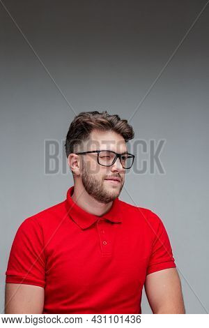 Stylish Young Guy Wink In Glasses, Studio Portrait On Gray. Myopia Correction By Spectacles, Ophthal