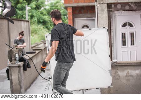 Behind The Scene. Filmmaking Lighting Technician Electric Engineer Adjusting Reflector And Setup Lig