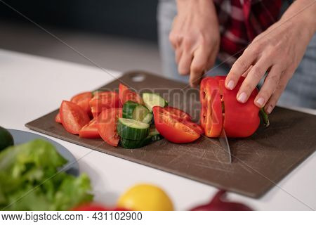 Cuts Vegetables For A Fresh Salad Young Housewife Cut Bell Pepper, Cucumber, Tomato On Cutting Board