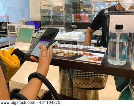 Women Uses Mobile Phone Application To Scan Qr Codes In Stores For Digital Payment.