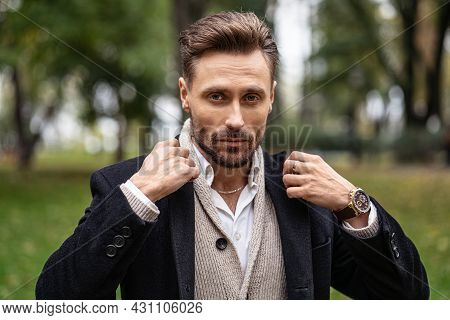 Adjusting The Collar Of A Dark Trench Coat Handsome Man Standing Outdoors In An Autumn Park Smiling