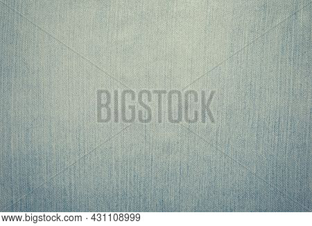 Worn and weathered blue jeans denim material background.