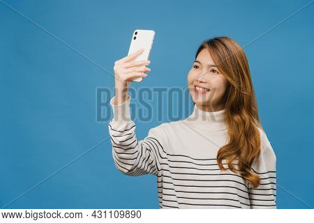 Smiling Adorable Asian Female Making Selfie Photo On Smart Phone With Positive Expression In Casual