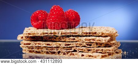 crackers and raspberry on blue