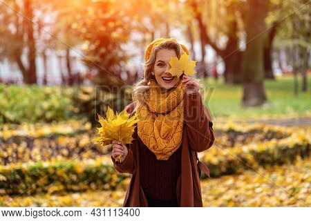 Happy Hiding Eye Woman With A Yellowed Leaf In Yellow Knitted Beret With Autumn Leaves In Hand And F