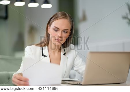 Portrait Of A Beautiful Businesswoman In White Jacket Working With Documents In Her Hands Sitting In