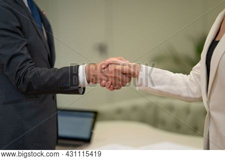 Female And Male Handshake. Young Freelancers Working Together Doing Handshake At Business Meeting At