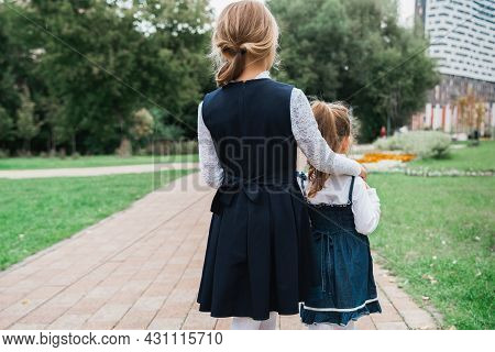 Back To Elementary School Concept. Little Girl In School Uniform Goes To First Grade With Little Sis