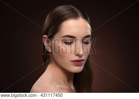 Strong And Lowered Gaze Close Up Portrait With No Make Up. Healthy Pure Skin Model Isolated On Black
