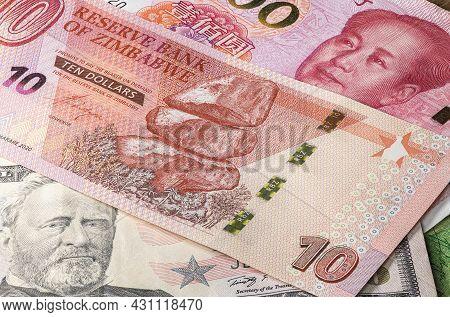 Close Up To 10 Dollars Of The Republic Of Zimbabwe Between 50 Us Dollar And 100 Yuan Banknotes. Ten