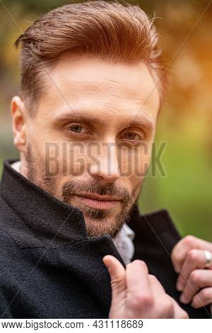Handsome Man Holding A Corner Of His Coat Standing On The Street In An Autumn Coat Smiling Looking A
