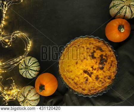Thanksgiving Dinner. Festive Table. Pumpkin Pie. Multi-colored Pumpkins And Lighted Lights. View Fro