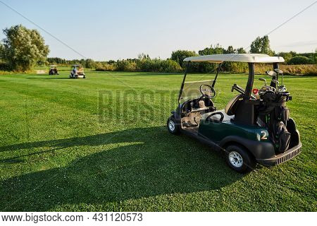Golf Car With Golf Clubs And Equipment Stands On Grass Golf Course With Long Shadow During Golfing