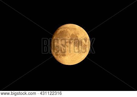 The Moon Shines With Soft Yellow Light In A Cloudless Black Sky. The Moon Is In The Last Quarter.
