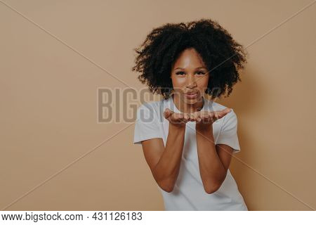Beautiful Curly Flirty African Woman In White T-shirt Sending Air Kiss And Smiling, Demonstrating Wa