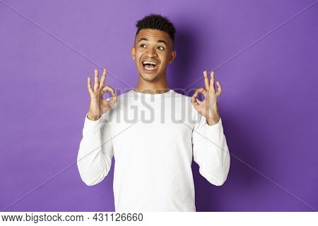 Image Of Satisfied African-american Male Student, Looking Pleased, Looking At Upper Left Corner And