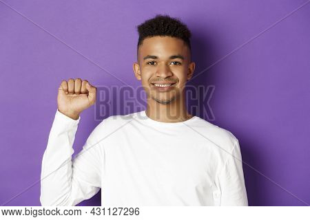 Close-up Of Handsome Smiling African-american Man, Looking Hopeful And Raising Fist, Showing Black L