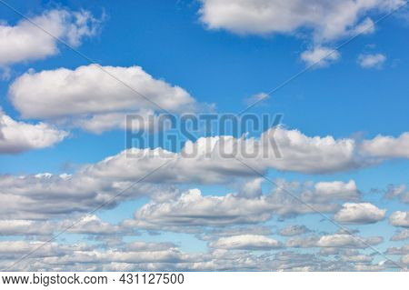 White Fluffy Clouds Float Across The Blue Sky During The Daytime. Copy Space.