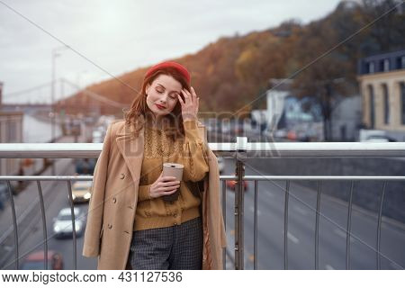 Woman With Coffee Mug On City Street. Charming Woman Enjoying Her Cup Of Coffee Standing In A Spring
