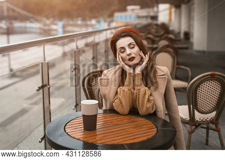 Parisian Woman With Coffee Mug On City Street In Evening. Charming Woman Enjoying Her Cup Of Coffee