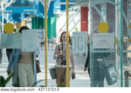 Moscow - May 24, 2021: Women in casual clothes walking towards pavilion entrance while preparing to take part in seminar