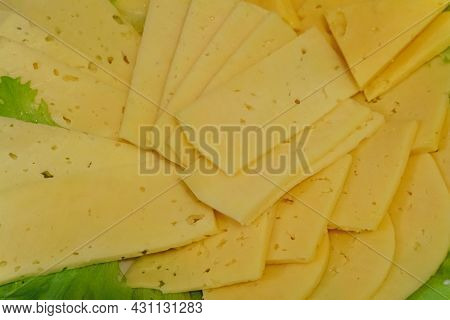 Sliced Slices Of Yellow Cream Cheese With Holes