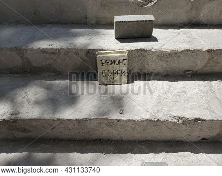 Old Stairs Renovation. Construction Background. Cement Steps With Brick And Text On Plate - Renovati