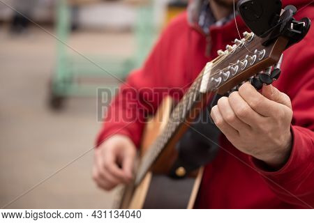 Close-up Of Male Hands Tuning A Classical Guitar Outdoors During The Day. The Guitarist Is Preparing