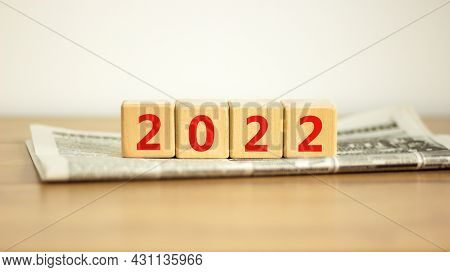 2022 Happy New Year Symbol. Wooden Cubes On Newspaper Symbolize The Change From 2021 To The New Year
