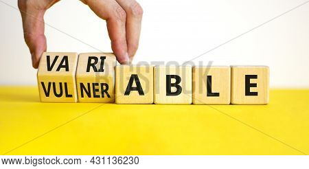 Vulnerable Or Variable Symbol. Businessman Turns Wooden Cubes And Changes The Word Vulnerable To Var