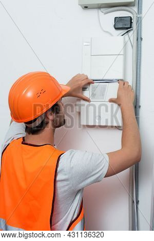 Young Repairman In Safety Vest Working With Switchboard