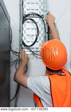 Back View Of Workman Standing Near Switchboard