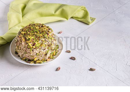 Sesame Halva With Pistachios On Top, Few Scattered Nuts, Green Linen Napkin And Copy Space. Turkish