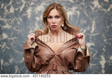 Glamorous middle-aged woman with enlarged full lips poses in a leather coat on a grunge background. Luxury lifestyle. Female beauty, fashion.
